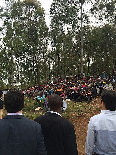 Wharton students learn from locals in a community meeting outside Kigali.